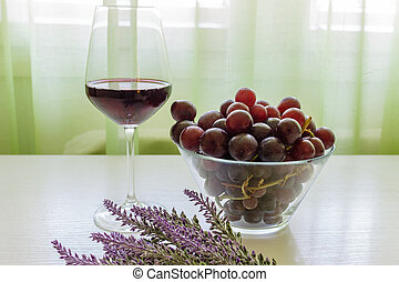 Glass of red wine, grapes and lavender on white wooden table