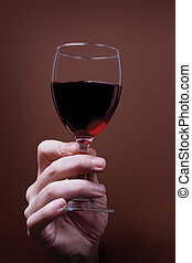 glass of red wine in hand on brown background