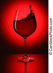 Glass of red wine on red background