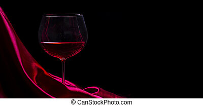 Glass of red wine on red silk against black background. Wine list design background.