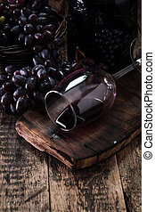 Glass of red wine, served with grapes on a wooden background
