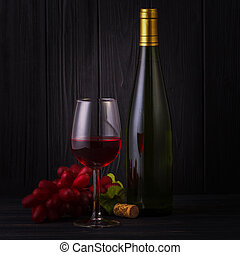 Glass of red wine with a bottle and grapes on back