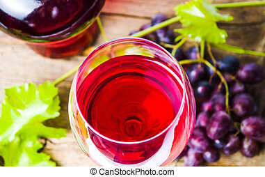 Glass of red wine with grape on rustic wooden background
