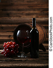 Glass of red wine with grapes on brown wooden background