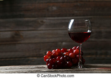 Glass of red wine with grapes on grey wooden background