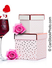 Glass of red wine with heart and pink gift box and rose for...