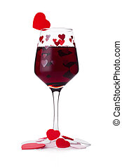 Glass of red wine with red and pink heart shape for...