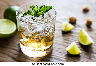 Glass of rum on the wooden background