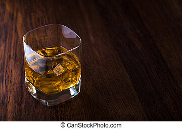 Glass of scotch whiskey and ice on a wooden background with ...