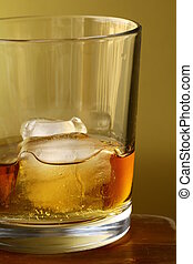 glass of scotch whiskey and ice on gold background