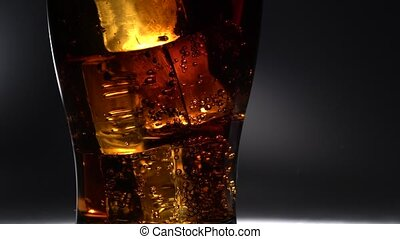 Glass of soda is on the table and bubbles burst out. light...