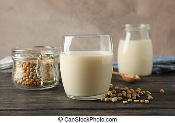Glass of soy milk, soybeans seeds on spoon, napkin on wooden background, space for text