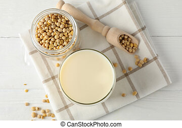 Glass of soy milk, soybeats seeds, napkin on white, wooden background, space for text. Top view