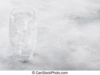 Glass of sparkling water lemonade drink with ice cubes and bubbles on stone kitchen table background.