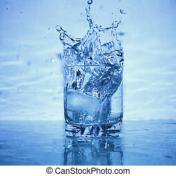 Glass of splashing water with ice on blue background