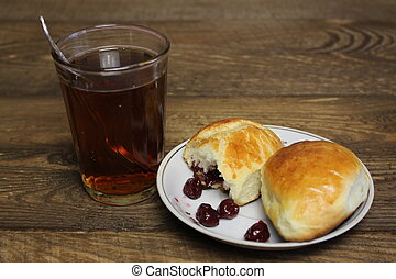 Glass of tea and cakes with cherries