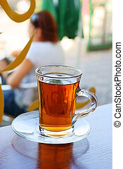 Glass of tea on table with blurred woman in background