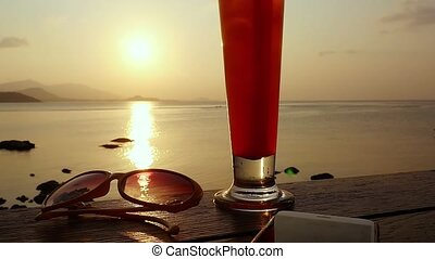 Glass of tequila sunrise cocktail standing on the wooden...