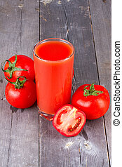 Glass of tomato juice and tomatoes on a wooden table