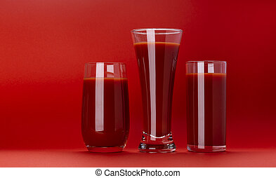 Glass of tomato juice isolated on red background with copy space