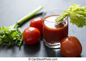 glass of tomato juice with celery, fresh tomatoes on black background