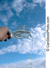 glass of water against a cloudy sky