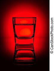 Glass of water, alcohol, vodka, juice or another drink on a rich dark red gradient background.