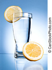 Glass of water and lemon on a blue background