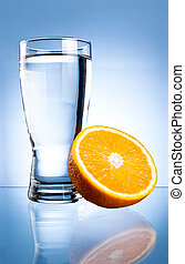 Glass of water and lemon on a blue