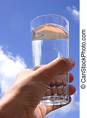 Glass of Water - Hand with glass of water and blue sky