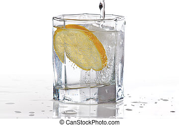 Glass of water, ice and slice of fresh lemon with splash on ...