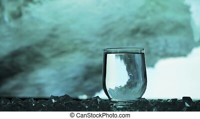 Glass of water on a background of river