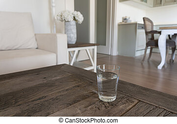 Glass of water on a wooden table in a living room