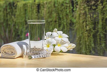 glass of water on a wooden table with white flower and...