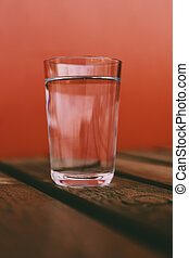 glass of water on wooden table with red background