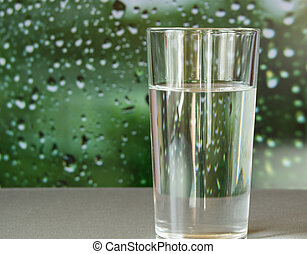 glass of water stands on a blurred green background with drops