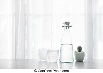 Glass of water with a bottle on table