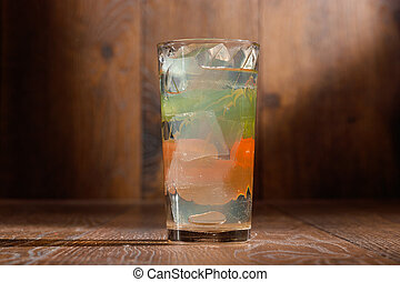 glass of water with ice on wood background.
