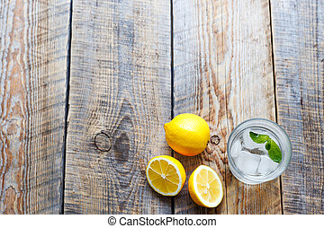glass of water with lemon and mint on wooden table