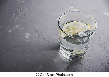 glass of water with lemon on grey background