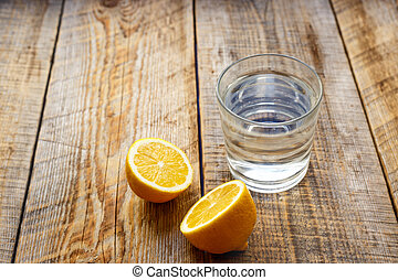 glass of water with lemon on wooden table