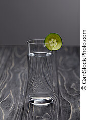 glass of water with piece of cucumber on grey background