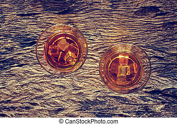Glass of whiskey bourbon with ice on wooden texture background.