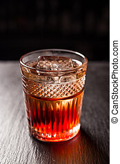 Glass of whiskey (cognac or brandy) with ice cubes standing on the bar counter
