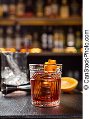 Glass of whiskey (cognac or brandy) with lemon and ice cubes standing on the bar counter with a bottle on the background