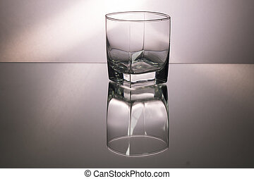 Glass of whiskey on mirroring table. Gorizontal image with copy space. Gray background