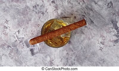 Glass of whiskey with ice cubes and cigar placed on top of...
