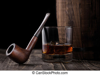 Glass of whiskey with ice cubes and vintage smoking pipe next to wooden barrel. Cognac brandy drink