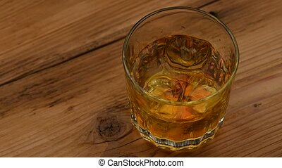 Glass of whiskey with ice cubes on table