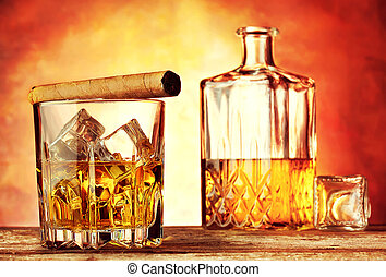 Glass of whiskey with ice flavored cigar